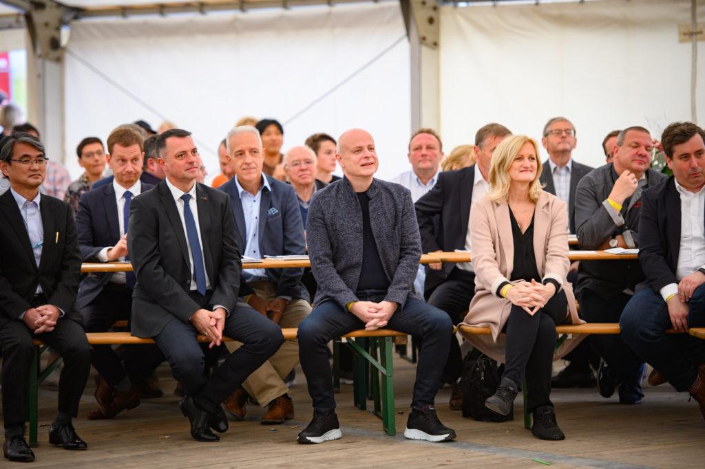 TDDK-Geschäftsführer Kazushige Murao, Ministerpräsident Michael Kretschmer, 1. Beigeordneter des Landrats Udo Witschas, Ministerpräsident a. D. Stanislaw Tillich, Bürgermeister Harry Habel (v. l. n. r.) und viele weitere Gäste feiern TDDKs 20. Geburtstag